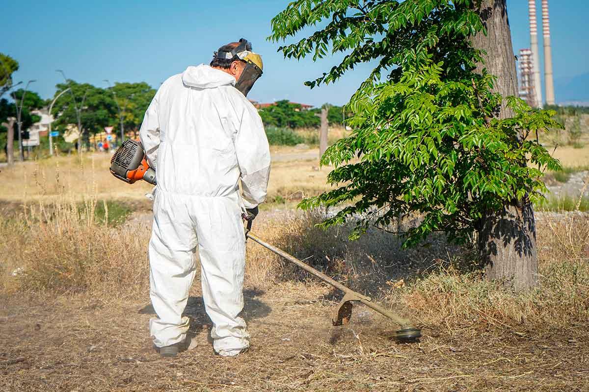 operatore Ecoross effettua operazione di diserbo di un'area pubblica